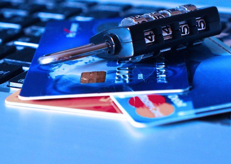 Um cadeado em cima de dois cartões de créditos acima de um teclado de notebook.