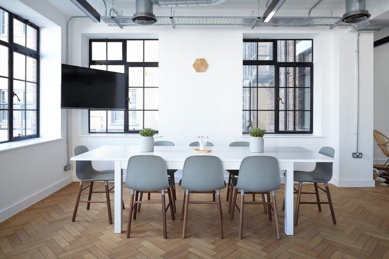 Imagem de cadeiras de plástico com pés de madeira em sala de estilo industrial com TV