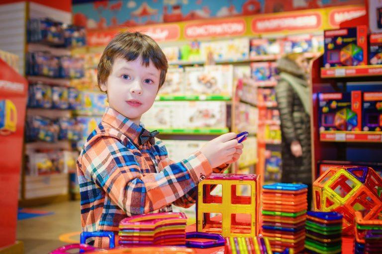 Na foto um menino dentro de uma loja de brinquedos.