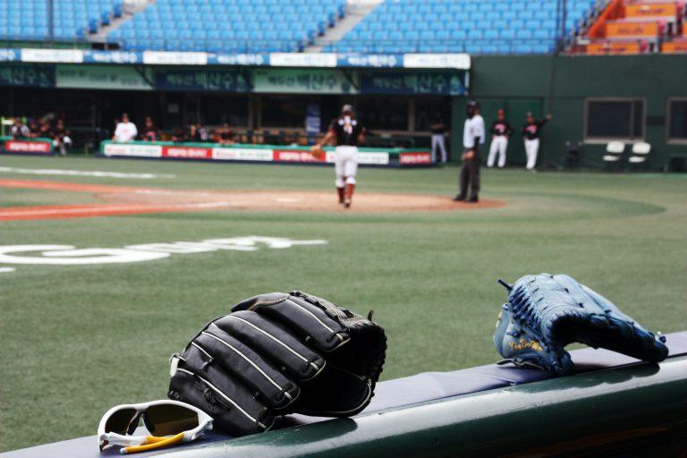 Imagem mostra duas luvas de beisebol em primeiro plano, repousando sob um banco. Ao fundo, o treino de uma equipe num estádio vazio.
