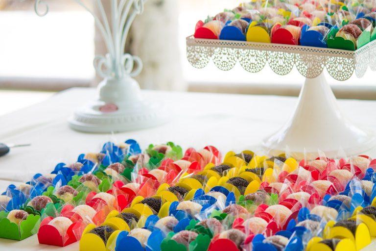 Na foto uma mesa com diversos doces de festa em forminhas coloridas.