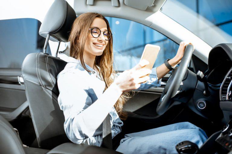 Uma mulher mexendo em um celular sentada no banco da frente do carro.