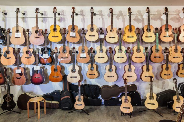 Imagem de diversos violões acomodados em suportes de parede e piso