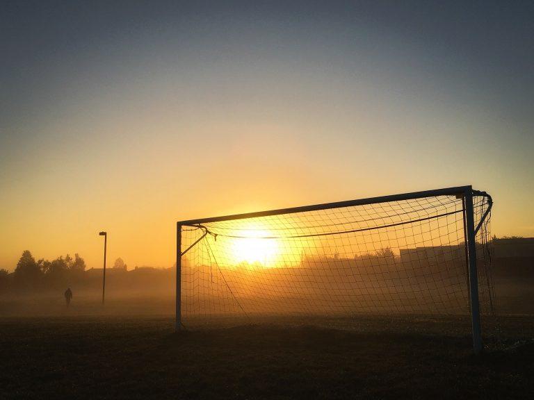 Imagem mostra um gol num campo vazio, iluminado pelo sol nascente.