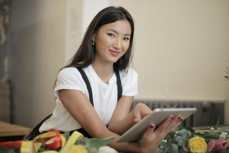 Imagem de uma mulher vendendo flores pela internet.