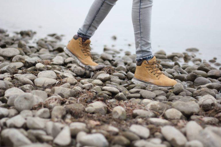 Imagem mostra as pernas de uma pessoa que calça botas, andando sobre pedras na beira de um lago, que fica discreto ao fundo, desfocado.