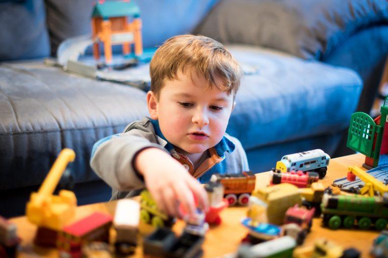 Na foto um menino brincando com diversos brinquedos.
