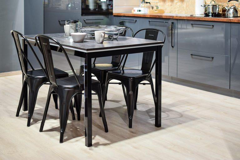 Imagem de cadeiras de plástico ao redor de uma mesa em uma cozinha