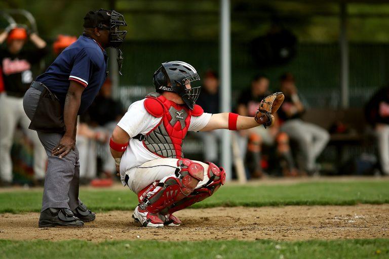 Imagem mostra um Catcher de beisebol de cócoras, com a mão direita atrás das costas e a mão esquerda, a da luva, estendida.