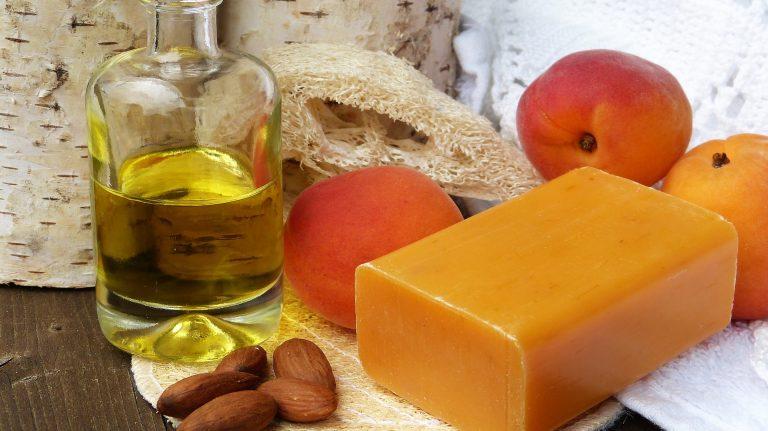 Óleo corporal ao lado de barra de sabonete, esponja, frutas e sementes
