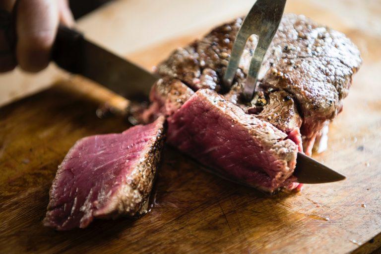 Na foto uma pessoa cortando um pedaço de carne de boi em cima de uma tábua de madeira.