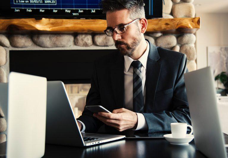 Homem trabalhando com notebook e celular.
