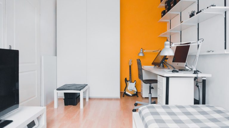 Imagem de quarto com suporte de guitarra compondo a decoração