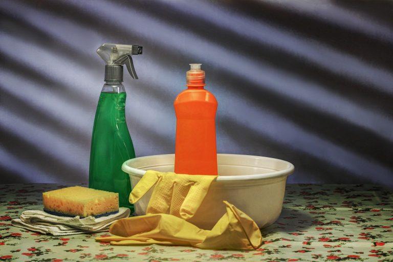 Imagem de tira manchas em borrifador junto de luvas, bacia e esponja