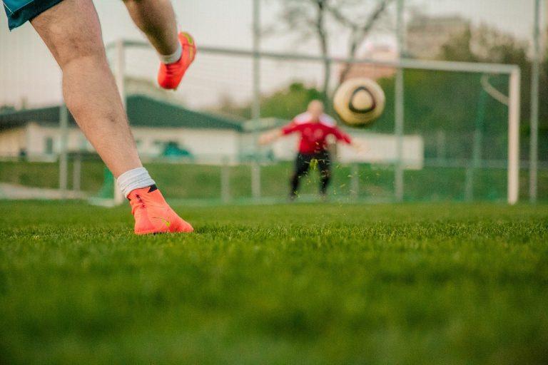 Imagem mostra o momento em que um chute é desferido na bola. Uma das pernas do batedor está no alto, enquanto a bola, em segundo plano, viaja em direção ao gol, onde podemos ver um goleiro desfocado se preparando para a defesa.