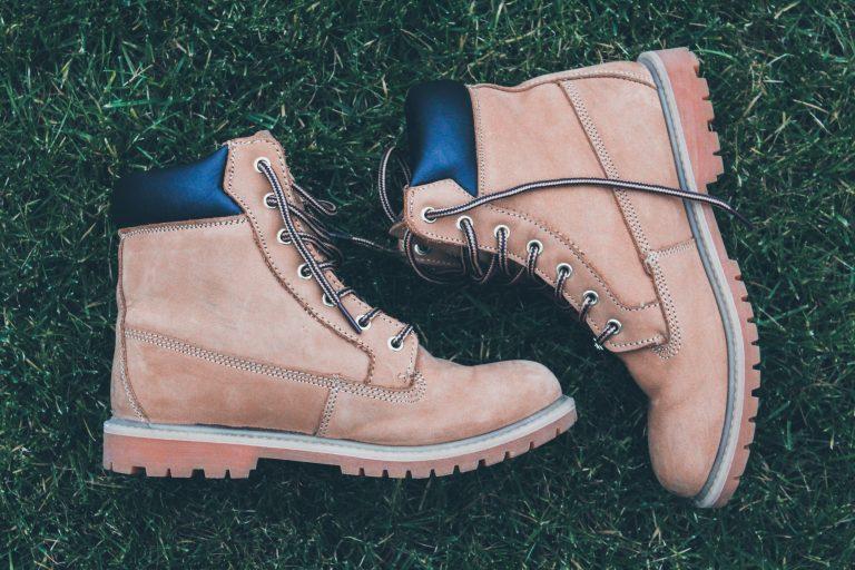 """Imagem mostra um par de botas sobre a grama, sem ninguém calçando-as. Elas estão deitadas, """"encarando"""" uma à outra."""