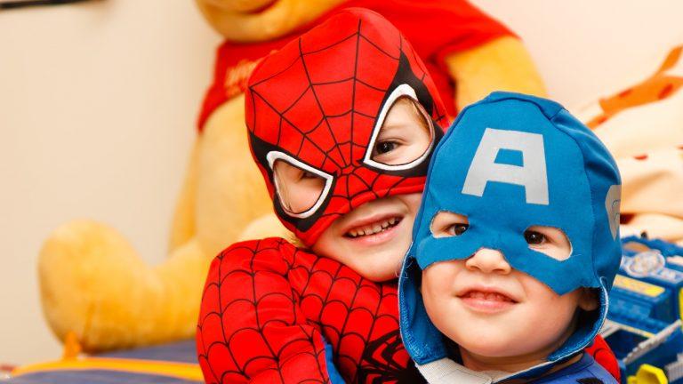 Na foto dois meninos fantasiados de Capitão América e Homem-Aranha