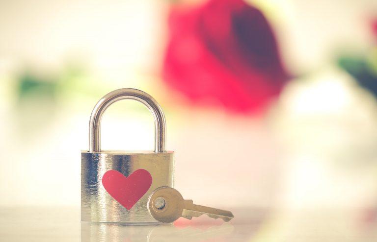 Um cadeado com um desenho de coração e uma chave em cima de uma mesa