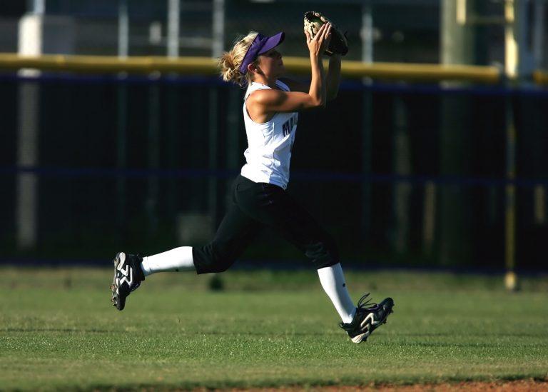 Imagem mostra uma jogadora de Softball apanhando uma bola durante o treino. Ela usa a luva na mão esquerda, mas usa a direita para auxiliar na recepção.