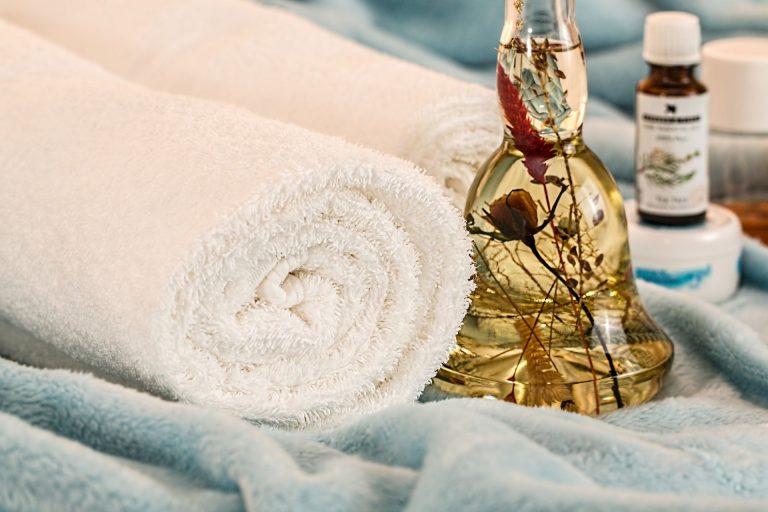 Frasco de óleo corporal em meio a toalhas