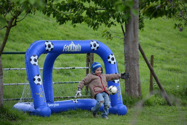 Imagem mostra um menino, com luvas de goleiro, no momento em que chuta a bola para longe do gol de traves infláveis que defende.