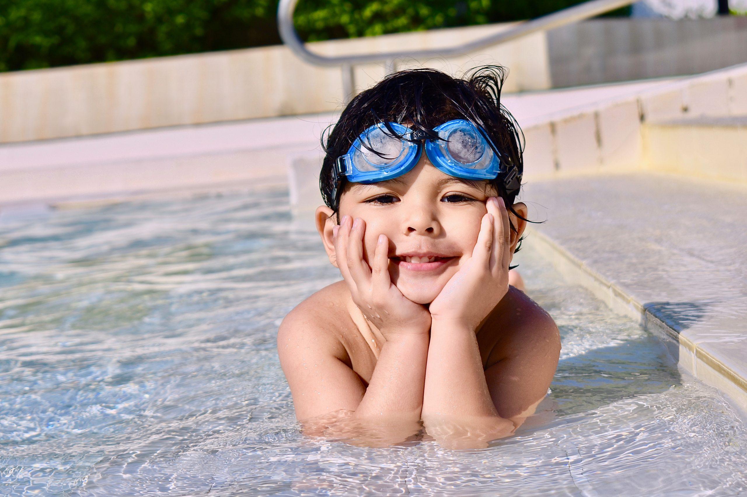 Imagem de uma criança utilizando óculos de natação.