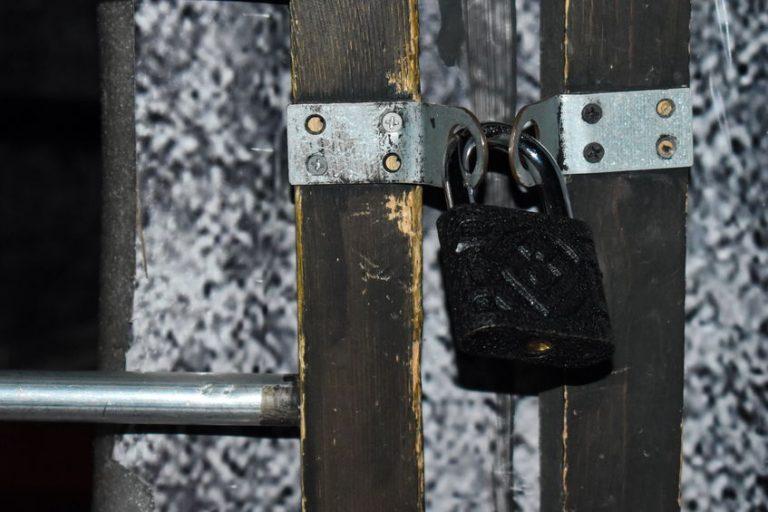 Uma máquina de cartão de crédito envolvida em uma corrente trancada por um cadeado com segredo. Ao lado esquerdo existem algumas moedas.