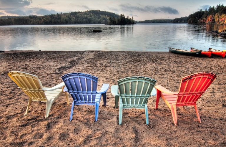 Imagem de cadeiras de plástico coloridas na areia diante de um rio