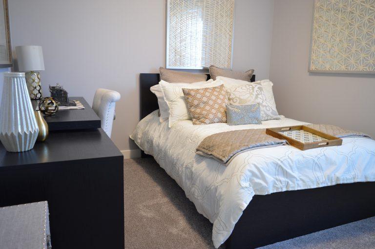 Imagem de quarto com cama coberta por edredom queen, almofadas decoradas e bandeja de madeira