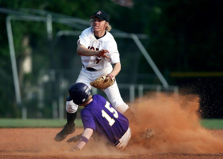 Imagem mostra uma disputa por uma base durante um jogo. Um adversário levanta poeira ao se jogar na base, o outro salta sobre ele após arremessar a bola.