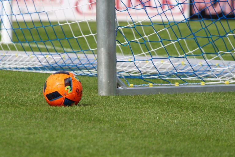 Imagem mostra um dos postes de uma trave de futebol de metal, montada sobre uma grama bem conservada. Ao seu lado há uma bola.