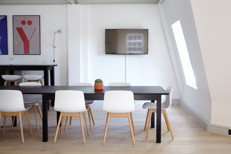 Imagem de cadeiras de plástico brancas com pés de madeira diante de mesa de madeira