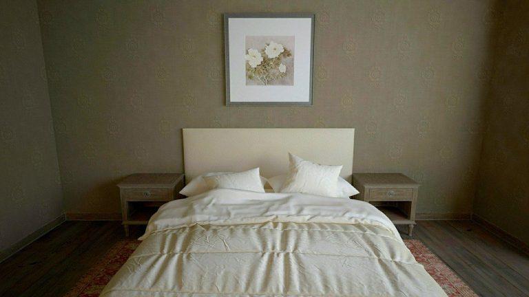 Imagem de quarto com cama coberta por edredom queen, criados e quadro de flores