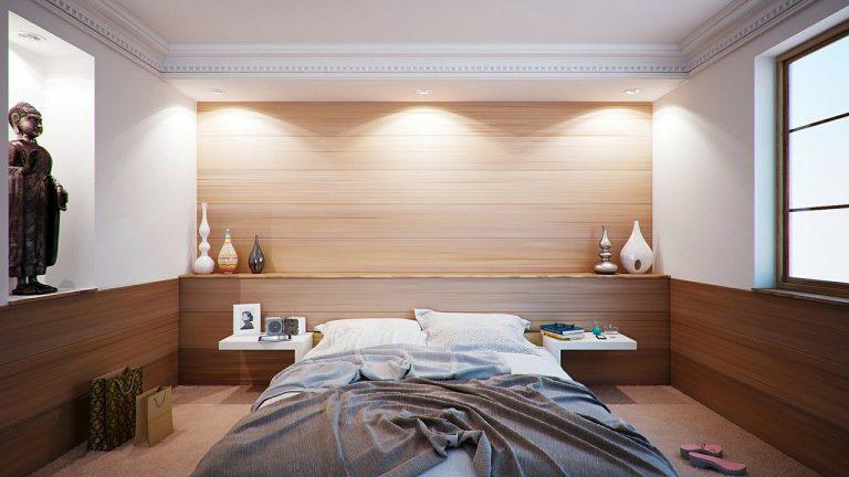 Imagem de quarto com cama coberta por edredom queen e criado com vaso de flores