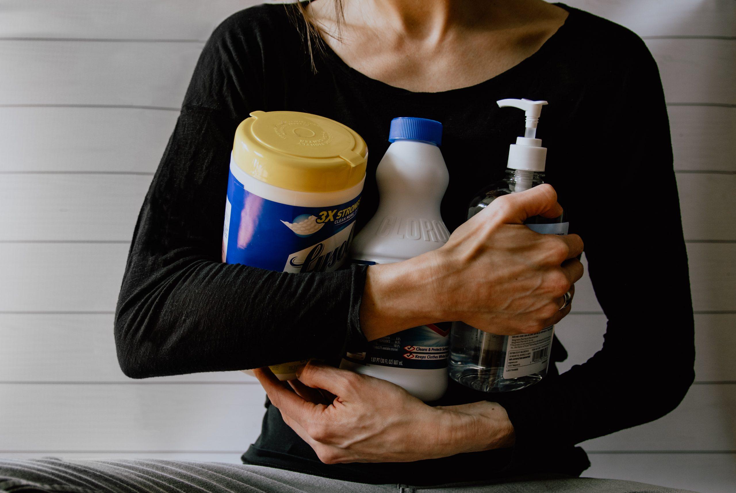 mulher segurando produtos de limpeza