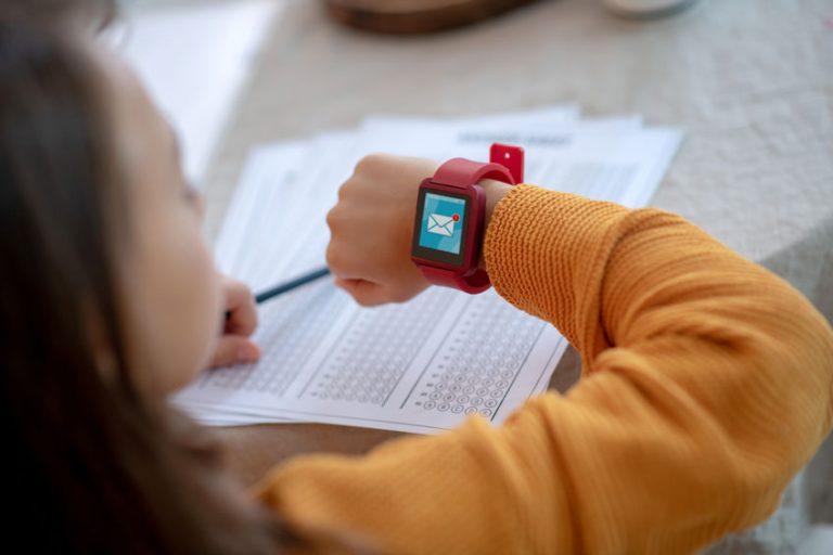 Menina olhando para o smartwatch infantil enquanto estuda.