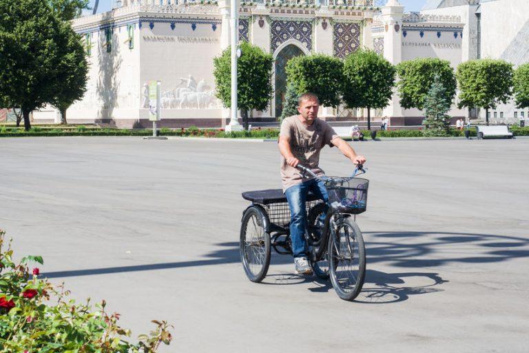 Imagem mostra um homem pedalando um triciclo em uma rua.