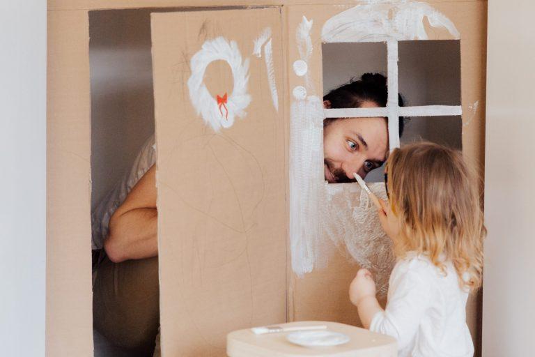 Criança pintando casinha de papelão com o pai.