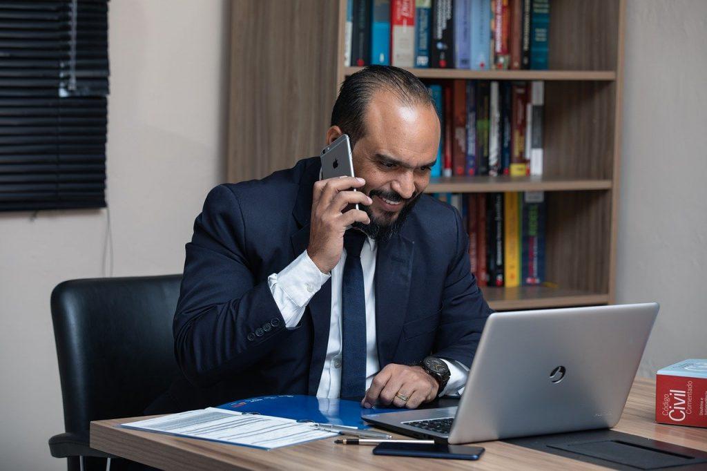 Homem de terno e gravata falando ao telefone, na mesa com notebook.