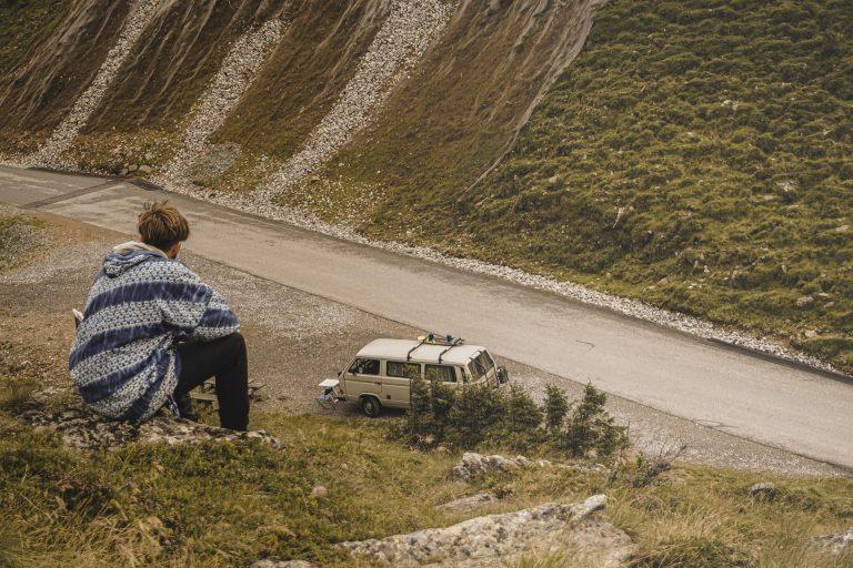 Imagem mostra uma pessoa acampando em um local isolado com um veículo ao fundo.