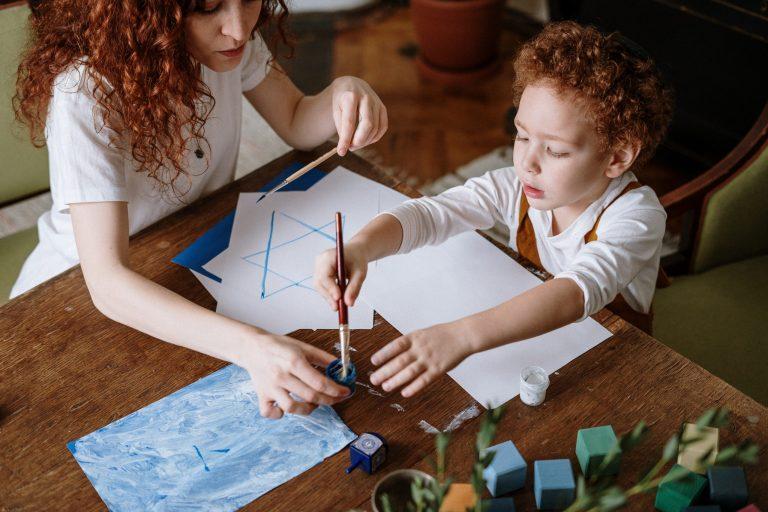 Mãe e filho pintando papel com tinta.