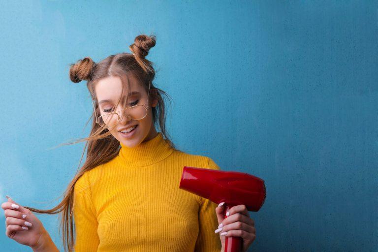 Mulher segurando um secador de cabelo vermelho.
