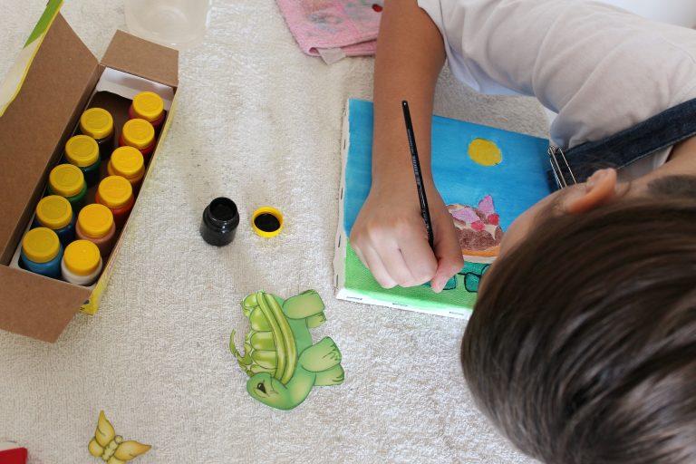 Criança pintando tela com tinta.