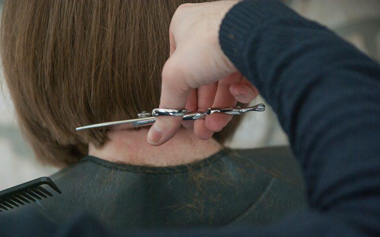 Pessoa cortando cabelo de mulher.