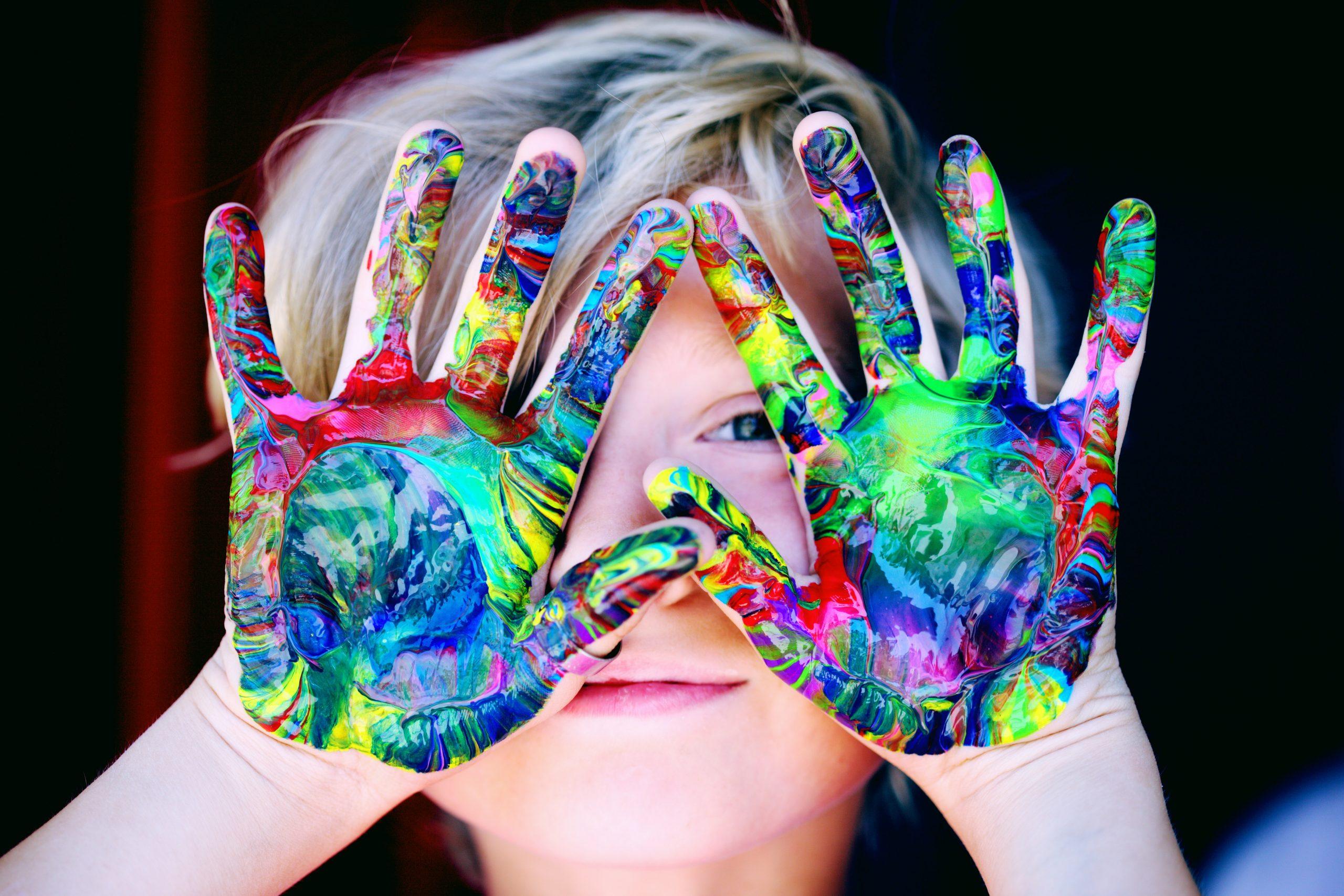 Criança com a mão pintada de tinta colorida.