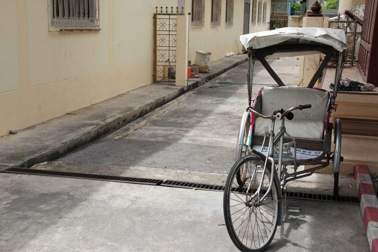Imagem mostra um triciclo com banco e cobertura.