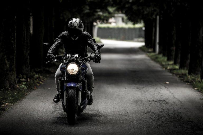 Imagem mostra uma pessoa andando de moto em uma estrada.