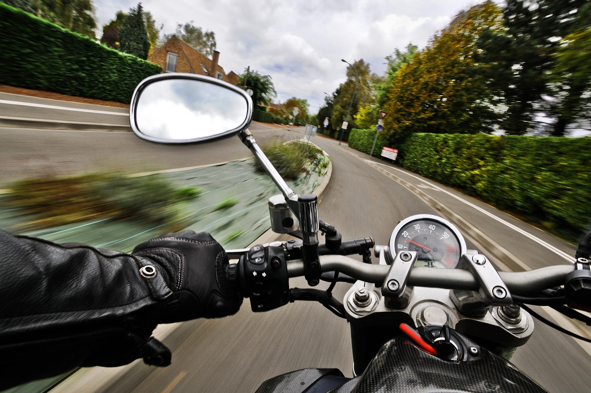 Imagem mostra uma moto em uma estrada com o retrovisor em destaque.