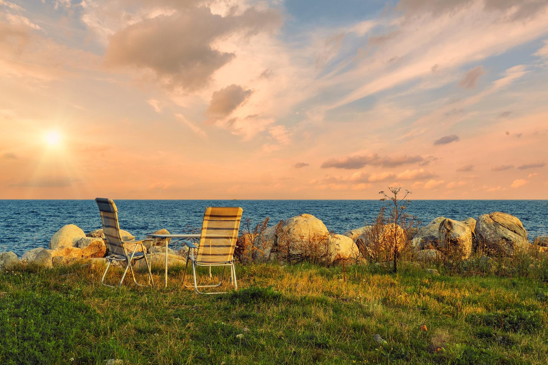 Imagem mostra duas cadeiras de camping e uma mesa em uma área verde.