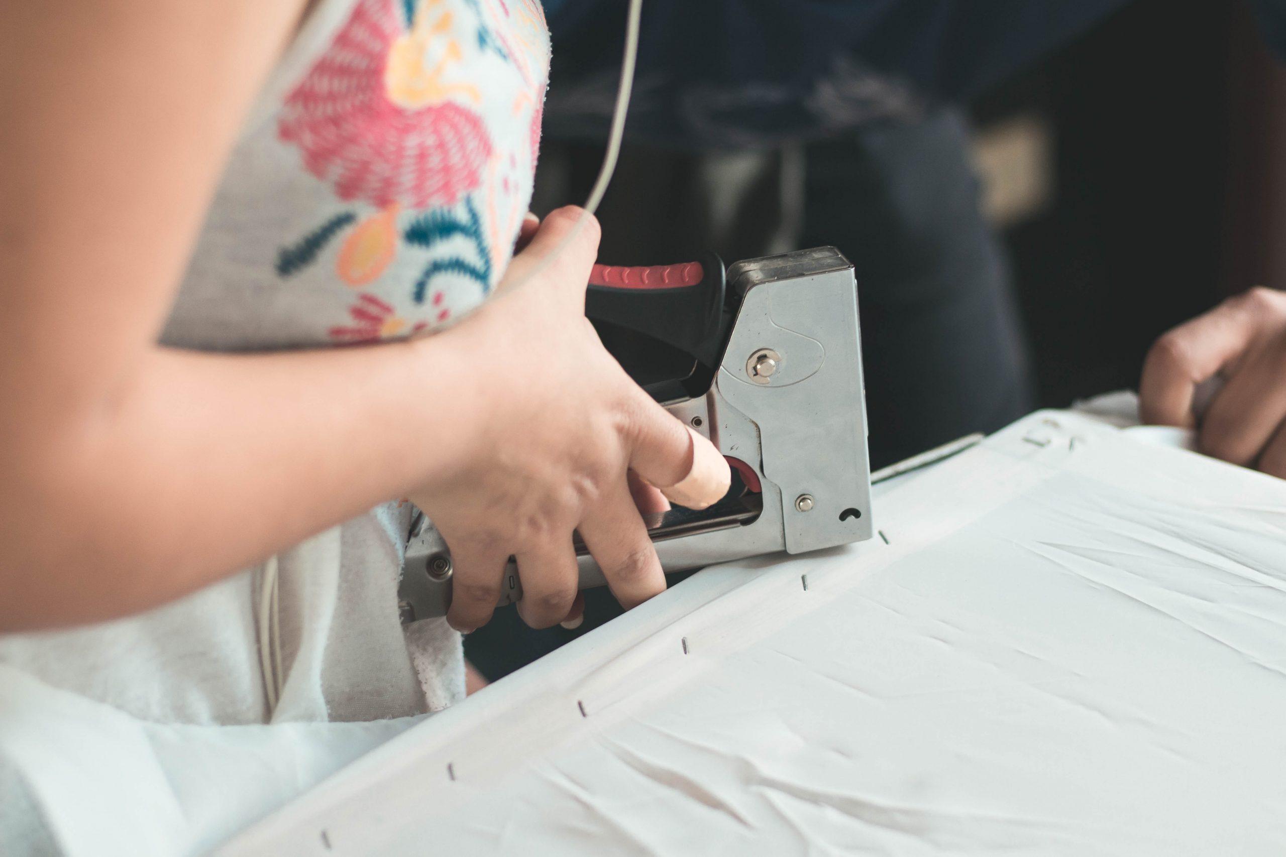 imagem de um grampeador tapeceiro sendo utilizado.